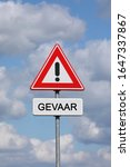 Small photo of A sign with a exclamation mark warning for a dangerous situation ahead and a smaller sign below with the Dutch word Gevaar on it, meaning danger in English