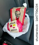Small photo of Rayong, Thailand - February 18 2020,KFC Zinger double cheese burger set place on a leather car seat in a car.