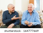 Smiling  Men Talking On  Couch