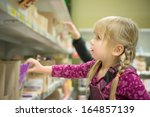 adorable girl select chocolate...   Shutterstock . vector #164857139