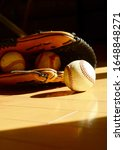 Baseballs And Gloves Sit On A...