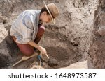 Archaeologist Digging With Hand ...
