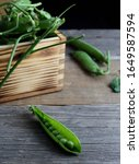 Small photo of peas with pod in the foreground, with wooden box background full of pods