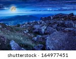 valley with stones on the mountain top under the moon - stock photo