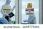 Small photo of coronavirus covid 19 quarantine and breakout alert sign on window of quarantine room at hospital with coronavirus covid19 disease control experts make disease treatment to coronavirus infected patient