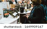 Small photo of Strasbourg, France - Feb 16, 2020: Woman lloking at the Vignerons independant English: Independent winemakers of France wine fair for private and horeca customers