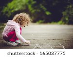 child draws on asphalt | Shutterstock . vector #165037775