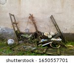 Small photo of Old rotten wooden shelves relented under the weight of kitchenware overgrown with grass and lianas. Canteen dishes in an old abandoned factory. - Image
