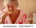 Small photo of Elderly grandmother in pink terry bathrobe brushes her teeth in bathroom. Hygienic procedures. Pensioners in sanatorium
