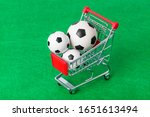 Soccer balls in shopping cart on green foorbal field