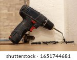 A black home electric screwdriver leaned against the wall. There are screws next to the screwdriver. Hand drill or screwdriver, electric cordless hand drill on wooden. Home maintenance concept - stock photo