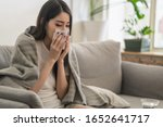 Small photo of Daily life or health problem concept : Young Asian woman caught a cold and have a running nose or fever have to rest at her home and absent from her job.