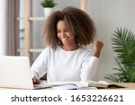 Small photo of Excited happy overjoyed african american teen school girl student winner celebrating victory reading admission email with good exam test results received great news online looking at laptop computer.