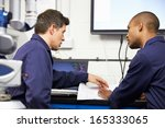 two engineers discussing plans... | Shutterstock . vector #165333065