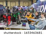 Small photo of KYIV, UKRAINE - APRIL 13, 2019: People playing computer games at Republic of Gamers booth, a brand used by Asus since 2006, encompassing a range of PC gaming. CEE 2019, electronics trade show.