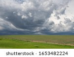 Landscape with dark storm clouds building in the sky over a recently planted field with a barbed wire fence during spring on North America's Great Plains.