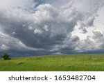 Landscape with dark storm clouds building in the sky over a vast green field with a wire fence during spring on North America's Great Plains.