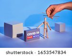 """Small photo of Covid19 novel coronavirus rumors. Sinister hand control wooden puppet on abstract geometric background. Box with text """"COVID-19 fake news"""". Beware of fake news about outbreak 2019-nCoV and treatment"""
