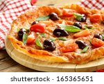 Italian pizza with olives and tomatoes on wooden board - stock photo