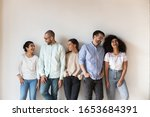 Small photo of Isolated on grey beige wall five cheerful multi-ethnic friends laughing enjoy live communication together, intimates warm relations, friendship racial equality, like-minded people having fun concept