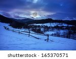 fence by the road to forest in the mountains on a fine winter day - stock photo