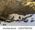 Man Hiking in Winter Snow at Maquoketa Caves State Park, Iowa- Natural Stone Land Bridge
