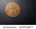 Reverse Side Of An Old English Copper One Pence Penny Coin From 1909 On Black Textured Background