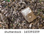 a hard drive resting on a pile... | Shutterstock . vector #165393359