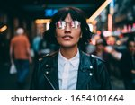 Small photo of Trendy dressed tourist in stylish eyeglasses with neon reflection looking up during evening sightseeing around metropolitan downtown, fashionable woman in spectacles hanging out in night city