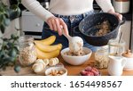 Woman Putting Oatmeal In A Bowl ...