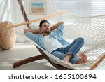 Young Man Relaxing In Hammock...