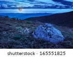 mountain panorama with large rock in grass on the hillside at night - stock photo