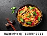 Small photo of Thai Drunken Noodles or Pad Kee Mao in black bowl at dark slate background. Drunken Noodles is thai cuisine dish with Rice Noodles, Chicken meat, Basil, sauces and vegetables. Thai Food. Copy space