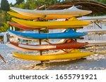 Colorful Kayaks On Stand. Sand...