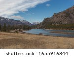 Curving river through evergreen tree valley with mountains and snow on clear day in rural Montana