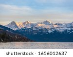 Stunning panorama view of famous Swiss Alps peaks on Bernese Oberland Eiger North Face, Monch, Jungfrau at sunset from Lake Thun (Thunersee) on a sunny autumn day with blue sky cloud,Bern, Switzerland - stock photo