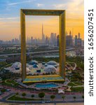 Small photo of Dubai, UAE - February 2020: Amazing sunset view of the world's largest frame made from gold in Dubai, UAE; Dubai frame at sunset featuring Dubai skyline on a cloudy day
