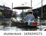 Small photo of Ratchaburi, Thailand, -December,1, 2012 : Folkway concept, vendor paddle wooden boat in the early morning at the Damnoen Saduak Floating Market,Ratchaburi, Thailand. It's top5 famous floating market.