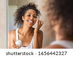 Small photo of Black girl take care of her beautiful skin. Young african woman applying moisturizer on her face. Smiling black natural girl holding little jar of skin lotion in bathroom for beauty treatment routine.