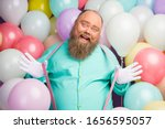 Small photo of Portrait of careless playful man funny funky hipster enjoy anniversary party celebration pull pink suspenders wear teal shirt over air baloons background