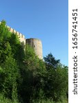 Small photo of high fortress walls overtop green trees