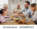Small photo of Happy extended family eating together and having fun during lunch time at dining table. Focus is on mid adult man.