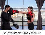 Young boxer woman hitting mitts ...