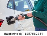 Old man with green sweater and jeans holding the compressed natural gas (CNG) hose to fill the tank of his eco-car. Sustainable energy concept. - stock photo