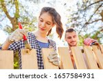 Small photo of Young woman and friend together in priming and varnishing wooden fence in the garden