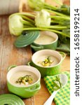 Small photo of Kohlrabi Potato Cream Soup in Portions on Wood with Whole Kohlrabi in the Background