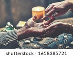 Small photo of Fortune teller woman wearing turquoise silver rings and bracelets reads palm lines during fortune telling to prediction the future around candles and magic accessories. Palmistry and divination