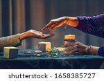 Small photo of Magic gypsy woman reading palm lines around candles and other magical accessories. Witch during fortune telling palmistry, prediction the future life and divination ritual