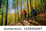 Small photo of Cycling woman and man riding on bikes at sunset mountains forest landscape. Couple cycling MTB enduro flow trail track. Outdoor sport activity.
