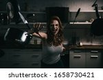 Small photo of demoniacal shouting girl gesturing with levitating kitchenware in kitchen